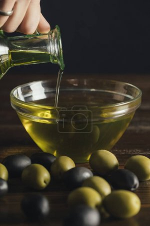 Photo for Cropped image of woman pouring olive oil from glass jar to bowl, olives on a table - Royalty Free Image