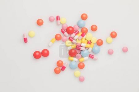 Photo pour Vue du dessus des pilules colorées dispersées isolées sur blanc - image libre de droit