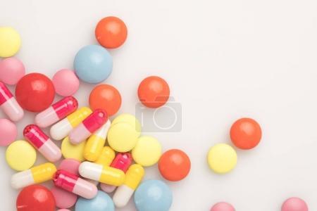 Photo pour Vue de dessus de pile dispersée de pilules colorées isolées sur blanc - image libre de droit
