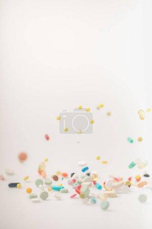 Photo pour Pilules colorées renversant et tombant sur une surface blanche - image libre de droit