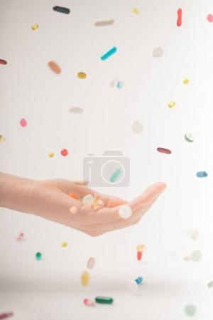 female hand catching falling pills