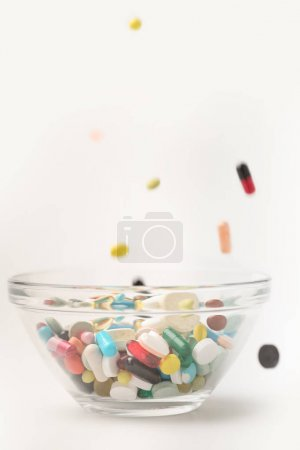 Pills falling into glass bowl