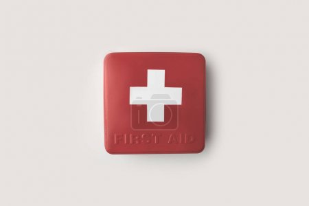 Top view of red first-aid kit with white cross isolated on white