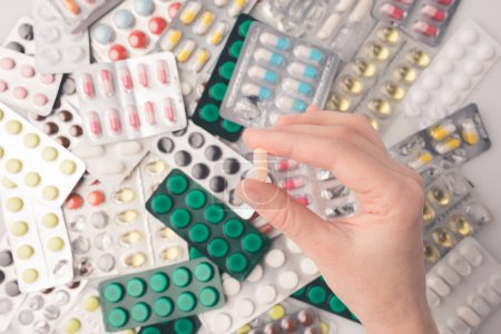 woman holding pill in hand