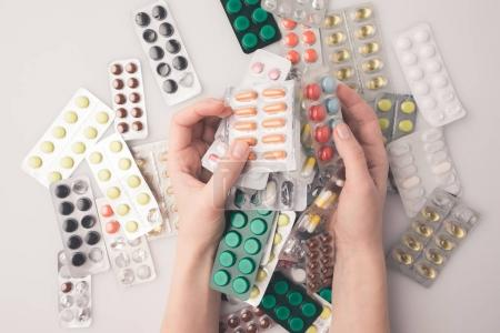 Photo for Cropped image of woman holding pile of blister packs with pills in hands - Royalty Free Image