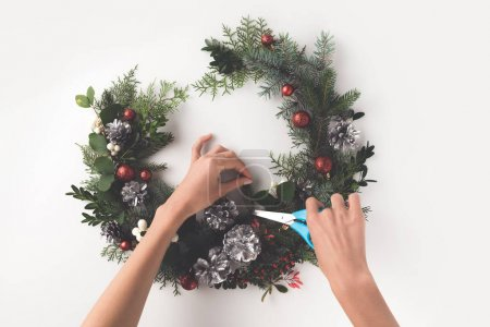 Photo for Cropped view of hand making christmas wreath from fir branches, christmas balls and pine cones with greeting card, isolated on white - Royalty Free Image