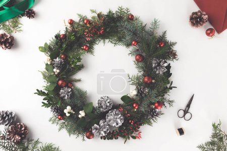 Photo for Top view of christmas wreath made of fir branches, christmas balls and pine cones with envelope, isolated on white - Royalty Free Image