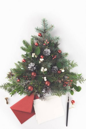 Photo pour Vue de dessus du sapin de Noël faite de branches de sapin, des boules de Noël et des cônes de pin avec la lettre et la plume, isolés sur blanc - image libre de droit