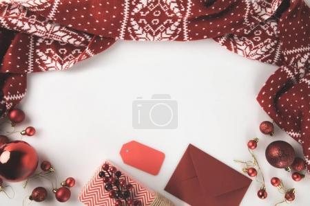 Photo for Top view of red christmas decorations with winter scarf, christmas balls, present and envelope, isolated on white - Royalty Free Image