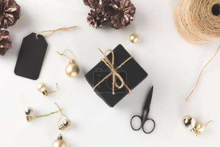Photo for Top view of black christmas gift box with tag, christmas balls, scissors and twine, isolated on white - Royalty Free Image