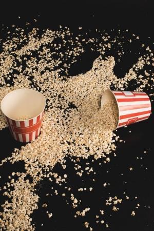 Popcorn spilled of cardboard buckets