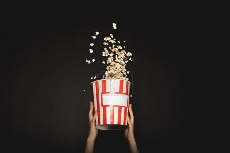 Photo for Cropped shot of woman holding bucket of tasty popcorn isolated on black - Royalty Free Image