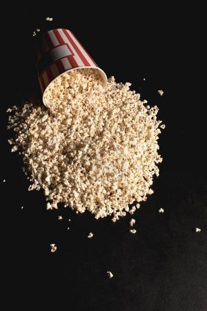 popcorn spilled from cardboard bucket