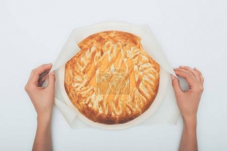 Photo for Top view of woman holding pumkin pie on parchment paper isolated on white - Royalty Free Image
