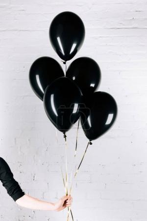 person holding black balloons