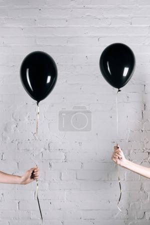 women holding black balloons