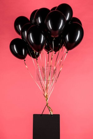shopping bag hanging on black balloons