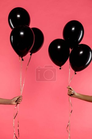 black balloons in hands