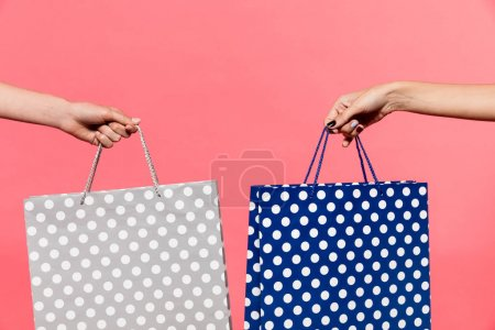 Photo for Cropped shot of women holding shopping bags decorated in polka dot isolated on red - Royalty Free Image