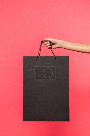 Photo pour Recadrée tir de détenteur de sac à provisions noir isolé sur pink - image libre de droit