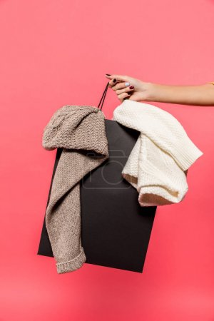 woman holding shopping bag with clothes