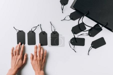 Photo for Partial view of female hands, black blank labels and shopping bag isolated on white - Royalty Free Image