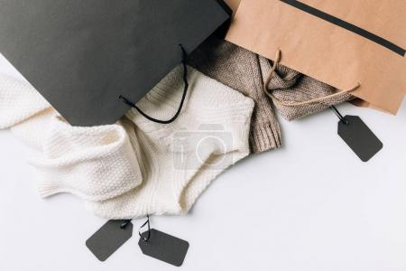Photo for Close-up view of shopping bags, clothes and blank labels on white - Royalty Free Image