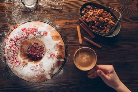 Photo for Cropped view of female hand with coffee on tabletop with homemade christmas cake, pecan nuts and cinnamon - Royalty Free Image