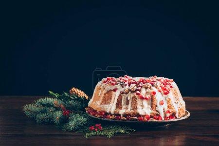 Photo pour Gâteau de Noël traditionnel avec grenade, noix de pécan et cerise sur une table en bois avec branche d'arbre de Noël - image libre de droit