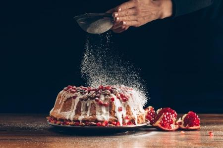 Photo for Cropped view of woman powdering traditional homemade pomegranate christmas cake with icing sugar - Royalty Free Image