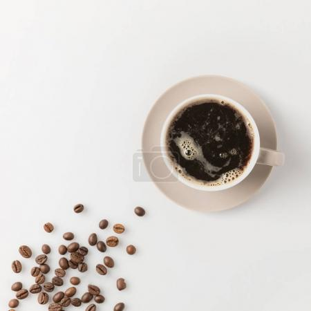 Photo for Top view of coffee cup with beans on white surface - Royalty Free Image