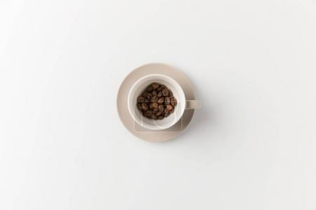Photo for Top view of cup with coffee beans on white surface - Royalty Free Image