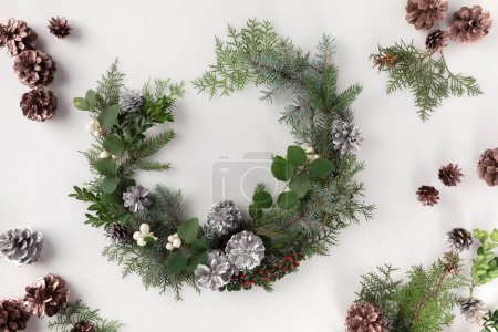 Photo for Christmas wreath made of fir branches, pine cones and mistletoe, isolated on white - Royalty Free Image