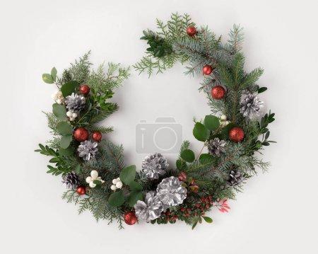 Foto de Corona de Navidad hecha de ramas de abeto, bolas de Navidad, conos de pino y muérdago, aislado en blanco - Imagen libre de derechos
