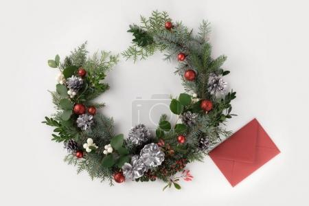Photo for Top view of christmas wreath made of fir branches, christmas balls and pine cones with red envelope, isolated on white - Royalty Free Image