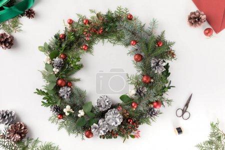 Photo pour Vue de dessus de guirlande de Noël faite de branches de sapin, des boules de Noël et des pommes de pin avec enveloppe, isolé sur blanc - image libre de droit