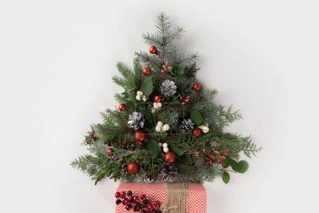 Foto de Vista de árbol de Navidad hecho de ramas de abeto, bolas de Navidad y piñas con presente, superior aislado en blanco - Imagen libre de derechos
