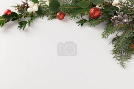 Photo for Top view of christmas fir branch with christmas balls, mistletoe and pine cones, isolated on white - Royalty Free Image