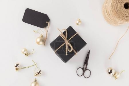 Foto de Vista superior de la caja negra de Regalo Navidad con etiquetas, bolas de Navidad, tijeras y guita, aislado en blanco - Imagen libre de derechos