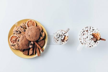 Photo for Top view of cookies and cups of hot cacao with marshmallows, on white - Royalty Free Image