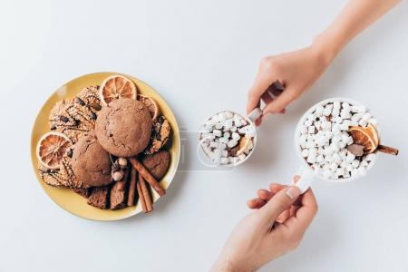 Photo for Cropped view of hands holding cups of hot cacao with marshmallows and cookies, isolated on white - Royalty Free Image