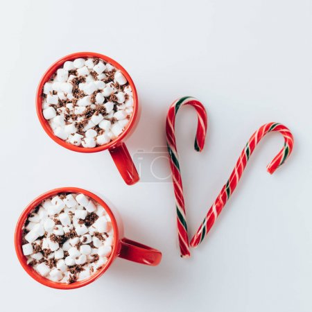 Photo for Top view of two cups of hot cacao with marshmallows and candy canes, on white - Royalty Free Image