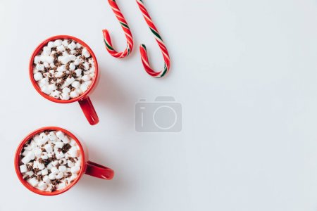 Photo for Top view of red cups of cacao with marshmallows and candy canes, on white - Royalty Free Image