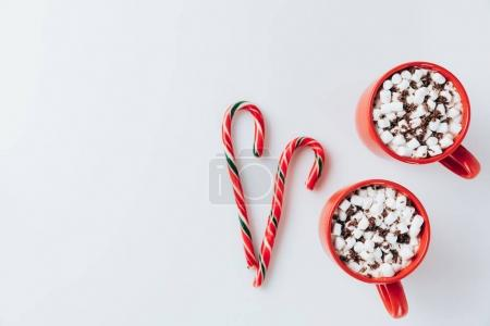 Photo for Top view of two cups of hot cacao with marshmallows and candy canes, isolated on white - Royalty Free Image