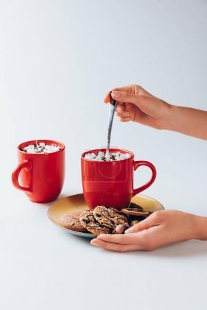 Photo pour Vue recadrée de mains avec une plaque à biscuits et les barquettes de cacao chaud avec des guimauves, sur blanc - image libre de droit