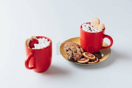 Photo for Plate with cookies and dried lemon with cups of hot cacao with marshmallows and gingerbreads, on white - Royalty Free Image