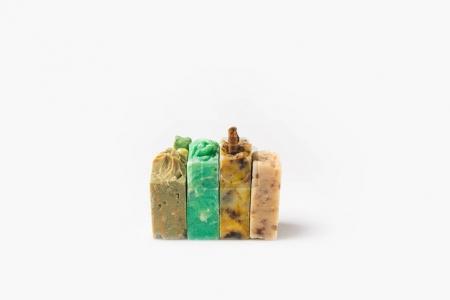 Photo pour Gros plan de divers savons fabriqués à la main debout en rangée sur une surface blanche - image libre de droit