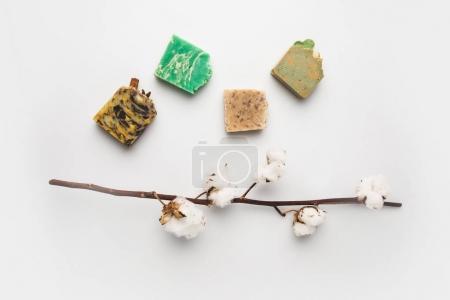 Photo pour Vue de dessus des barres de savon naturel différent avec la branche de coton sur la surface blanche - image libre de droit