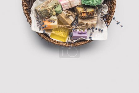 Photo pour Vue de dessus de divers savon artisanal dans le panier sur la surface blanche - image libre de droit