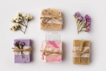 Photo pour Vue de dessus du savon fait maison décoré avec des fleurs sur la surface blanche - image libre de droit